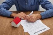 Fotografie Oříznout záběr člověka podpisu pojištění formulář na dřevěný stůl s modelem domu