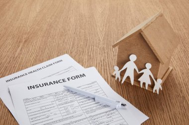 close-up view of insurance form, insurance health claim form, pen, small house and paper cut family on wooden table