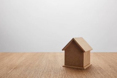 close-up view of small house model on wooden table on grey, insurance concept