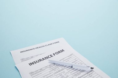 Close-up view of insurance form, insurance health claim form and pen isolated on blue stock vector