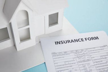 Close-up view of insurance form and small house model on blue stock vector