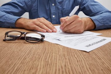 cropped shot of man signing insurance form at wooden table