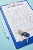 Fotografia close-up view of insurance form, pen and keys isolated on blue