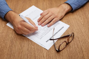 close-up partial view of person signing insurance form at wooden table