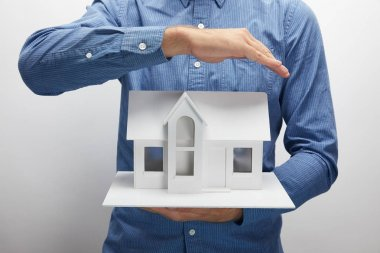 cropped shot of man holding small house model on grey, insurance concept