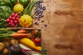 Organic raw vegetables in basket on wooden table