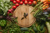 Fotografie Variety of fresh vegetables and herbs by cutting board on wooden table
