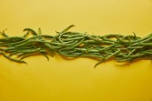 Green beans in a row on yellow background