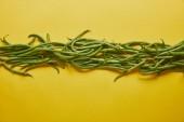 Grüne Bohnen in einer Reihe auf gelbem Hintergrund
