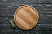 Vágódeszka és uborka, sötét fából készült asztal