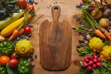 Cutting board with summer vegetables on wooden table