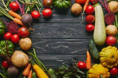 Frame of healthy summer vegetables on dark wooden table