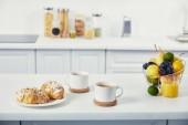 zblízka pohled šálků kávy a croissanty k snídani na bílém stole v kuchyni