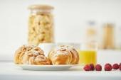 Fotografie zblízka pohled na čerstvě upečené croissanty a maliny na snídani na bílý povrch
