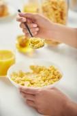Fotografie částečný pohled ženy s lžící sedí u stolu s corn flakes a sklenici šťávy k snídani