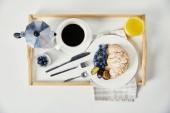 pohled shora croissant s čerstvými borůvkami a Švestkové kusů, sklenice šťávy, šálek kávy a jogurt na dřevěný tác na snídani na bílém stole