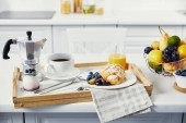 Fotografie close up view of tasty breakfast with cup of coffee and glass of juice on wooden tray on white surface
