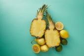 Fotografie elevated view of cut pineapple, pears and lemons on turquoise surface
