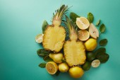 Fotografie top view of cut pineapple, pears and limes on turquoise surface