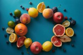 top view of circle of fruits on blue surface