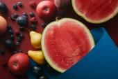 pohled ze zralého ovoce a modrého papíru na červené ploše