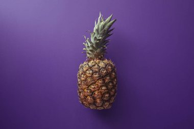 top view of pineapple on violet surface