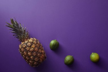 top view of pineapple and limes on violet surface