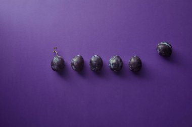top view of ripe plums on violet surface