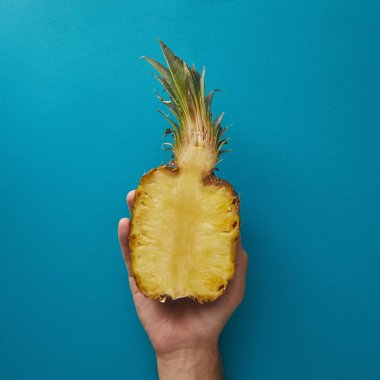 cropped image of man holding half of ripe pineapple above blue surface