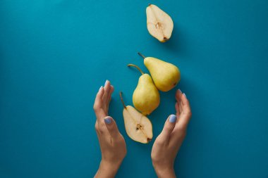 cropped image of woman holding hands near pears above blue surface