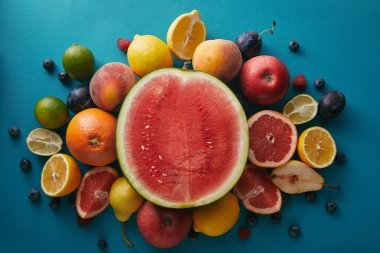 top view of watermelon and other different fruits on blue surface