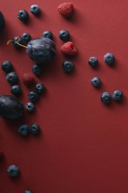 elevated view of blueberries, raspberries and plums on red surface