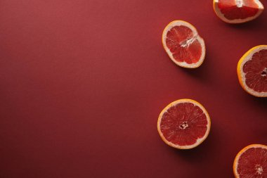 top view of cut grapefruits on red surface