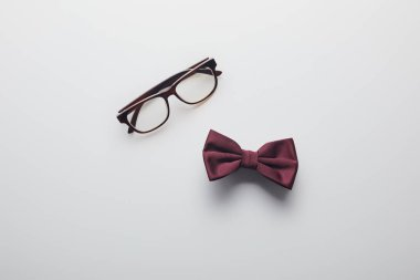 Top view of burgundy bow tie and eyeglasses isolated on white stock vector