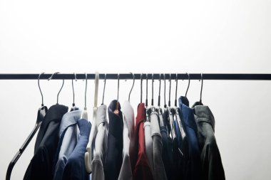 row of different shirts on hangers isolated on white