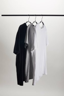 black, grey and white shirts on hangers isolated on white