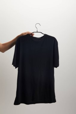 cropped image of woman holding hanger with black shirt isolated on white