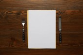Fotografie pohled shora na prázdnou kartu, vidlička a nůž na dřevěný stůl