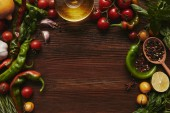 top view of oil, seasonings and vegetables on wooden background