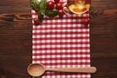 Fotografie top view of checkered tablecloth, wooden spoon and fresh basil with tomatoes and oil on wooden surface