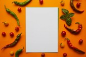 Fotografie top view of blank card and fresh tomatoes with basil and peppers on orange