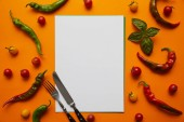 Fotografie top view of blank card, cutlery and fresh tomatoes with basil and peppers on orange