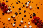 Fotografie top view of fresh champignon mushrooms, tomatoes, peppercorns and haricot beans on orange