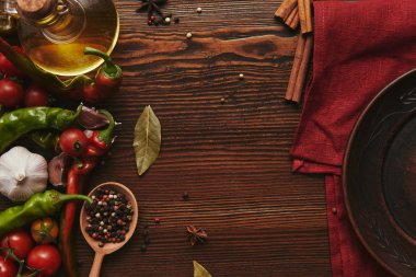 top view of red tablecloth, round plate, spices and vegetables on wooden surface