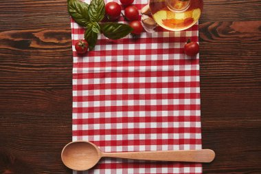 top view of checkered tablecloth, wooden spoon and fresh basil with tomatoes and oil on wooden surface