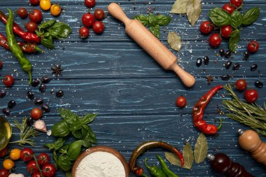 top view of fresh raw vegetables, spices and rolling pin on wooden surface