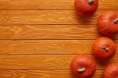 top view of whole ripe pumpkins on wooden background