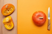 pohled shora celé a plátky dýně a nůž na oranžové a dřevěný povrch