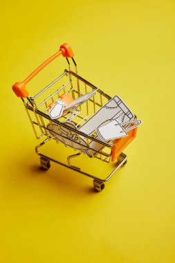 Close up view of little shopping cart with clothes made of paper on yellow background stock vector