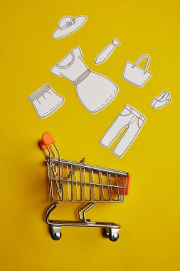 top view of little shopping trolley with paper clothes on yellow backdrop